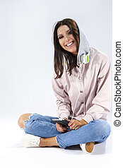 Modern Lifestyle Concepts. Funny Laughing Caucasian Brunette Girl With Smartphone and a Pair of Headphones. Posing in Hoodie and Blue Jeans Against White