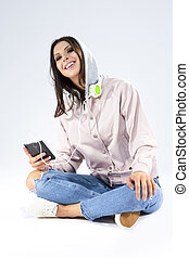 Modern Lifestyle Concepts. Funny Laughing Caucasian Brunette Girl With Smartphone and a Pair of Headphones. Posing in Hoodie and Blue Jeans Against White.