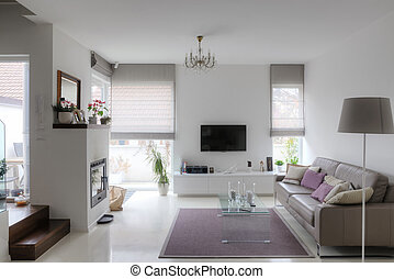 modern living room with taupe sofa glass table and fireplace