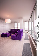 Violet hassock and couch in modern living room