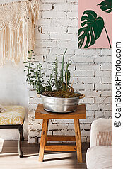 Modern loft interior with flowers in big metal pot. White brick wall on background