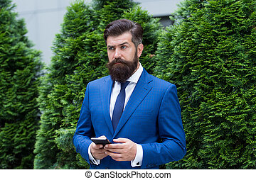 modern look of ceo. responding email. always online. have some problems. serious businessman with smartphone. agile business. confident bearded business man using modern technology. Useful nowadays
