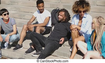 Modern lounging friends on steps - Cool young multiethnic...