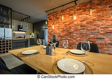 Modern luxurious dark gray and black kitchen with dining table