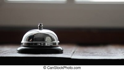 Hand strikes the bell on hotel reception - Modern luxury...