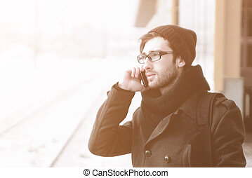 modern man talking on a mobile phone on the street in the winter day