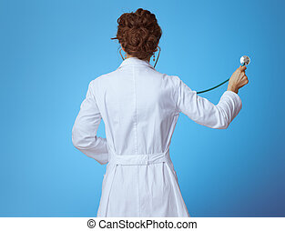 modern medical doctor woman listening with stethoscope on blue