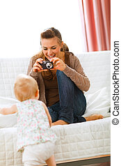 Modern mother making photos of baby