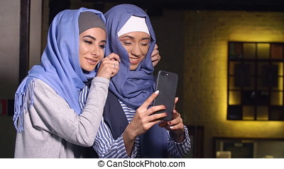 Modern Muslim women take pictures on a mobile phone. Girls in hijabs talking and smiling