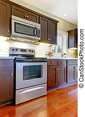 Modern new brown kitchen stove and microwave with cherry floor.