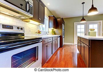 Modern new brown kitchen with cherry floor.