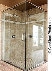 Modern new glass walk in shower with beige tiles.