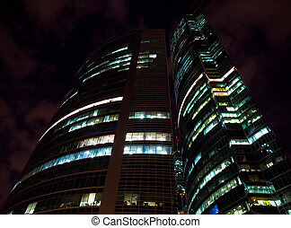 modern office building at night, skyscraper in moscow, foreshortening from below