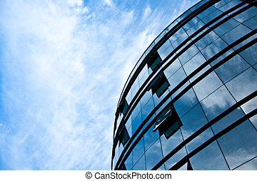 modern office building glass facade with reflection of sky and cloudy sky