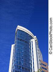 Modern office building over blue sky.