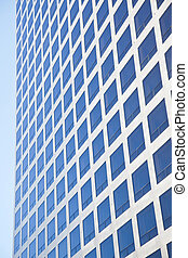modern office building reflecting blue sky in many square...