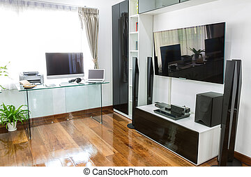 Modern office with computer and laptop with home theater