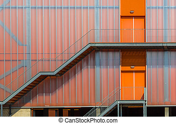 Modern orange building exterior with Emergency exit escape ...