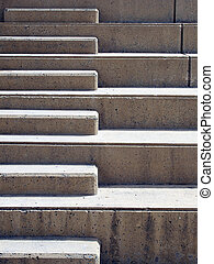 Modern outdoor concrete ascending steps with raised area for seating in contrasting sunlight and shadow