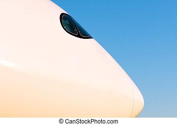 Modern passenger airplane nose side profile cockpit in evening light sunset blue sky.