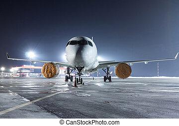 Modern passenger jet plane on the night airport apron