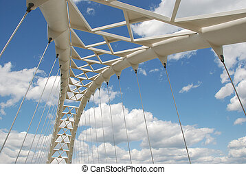 Modern pedestrian bridge against blue cloudy sky - Humber Bay Park in Toronto.
