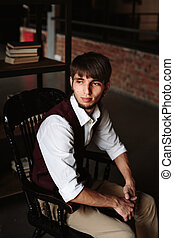 Bearded Man Sitting on a Chair in Loft Interior