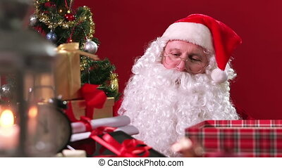 Modern Present - Cheerful Santa Claus putting a digital...