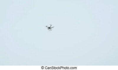 Modern quadcopter with camera flying in the sky in overcast...
