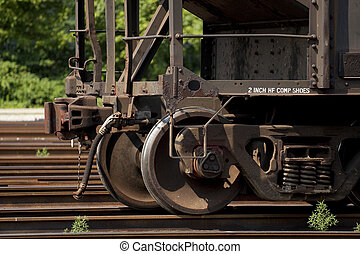 """Close-up view of a railroad car """"wheels"""" and coupler in a rail yard in West Virginia. These sets of """"wheels"""" on train cars are known as railroad trucks in the rail industry."""