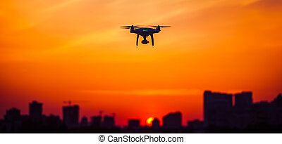 Modern Remote Control Air Drone Fly high with action camera in sunset sky