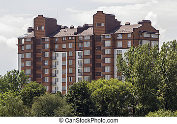 Modern residential apartment building among green trees. Property in ecological quiet area concept.