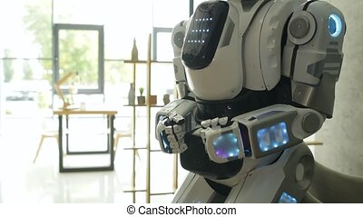 Modern robotic machine standing in office - Contemporary...