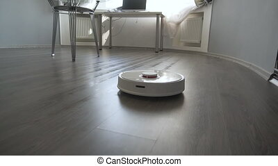 Modern robotic vacuum cleaner cleans the floor in the living...