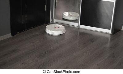 Modern robotic vacuum cleaner cleans the laminate floor....