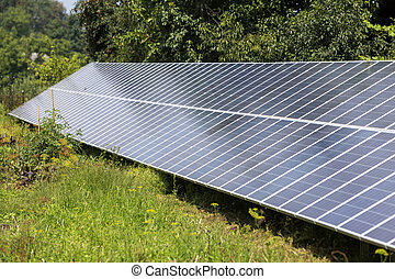 Modern saving efficient stand -alone blue shiny solar photo voltaic panels system producing renewable clean green energy in green grass on shingled cottage roof, green trees and blue sky background.