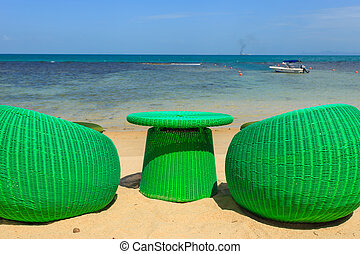 Modern seats stand on the beack, tropical sea and blue sky...