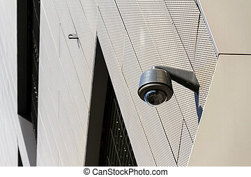 Modern security camera attached to wall with windows in background