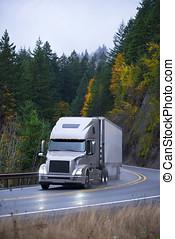 Modern semi truck trailer in rain autumn winding road -...