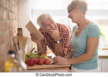 Modern senior couple spending time in the kitchen