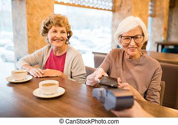 Modern senior ladies paying with smartphone