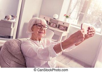 Modern senior taking selfie with her mobile phone