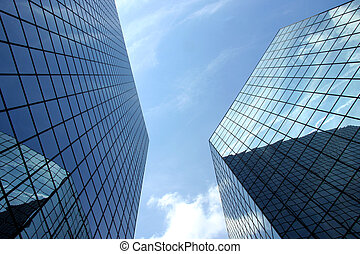 A upward perspective of two very modern skyscrapers