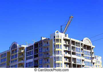 modern skyscraper with hoisting crane