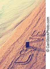 Modern smart phone on the beach with love text