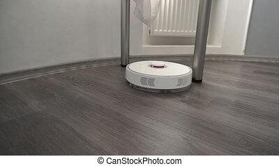Modern smart robotic vacuum cleaner cleans the laminate...