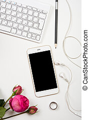 Modern smartphone, computer keyboard and fesh pink flowers on white table, freelancer blogger workspace, screen mockup