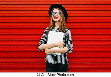 Modern smiling young woman with laptop looking away on red wall street background