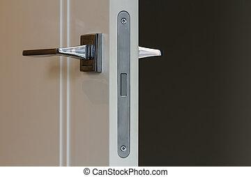Modern stainless steel door handle on white wooden doors