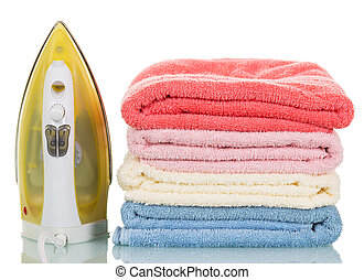 Modern steam iron and stack towels isolated on white background.
